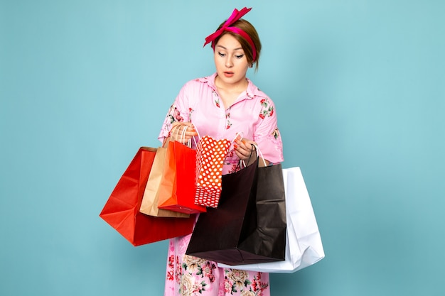 Молодая дама в розовом платье, вид спереди, позирует, держа пакеты с покупками на синем