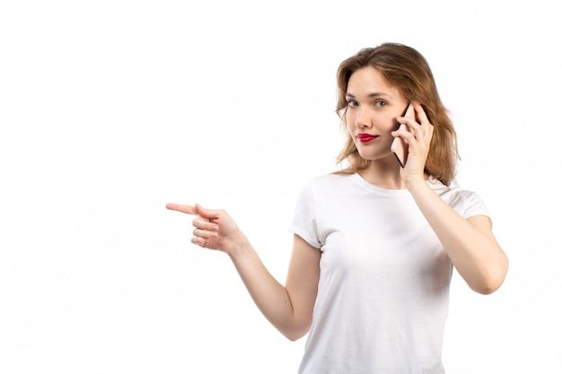 Вид спереди молодая леди в белой рубашке и черных современных джинсах позирует говорить по телефону на белом