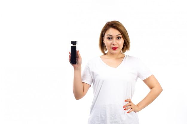 Вид спереди молодая леди в белой футболке с черным флаконом духов на белом