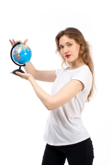 白の小さな丸い地球儀を保持している白いtシャツの正面の若い女性