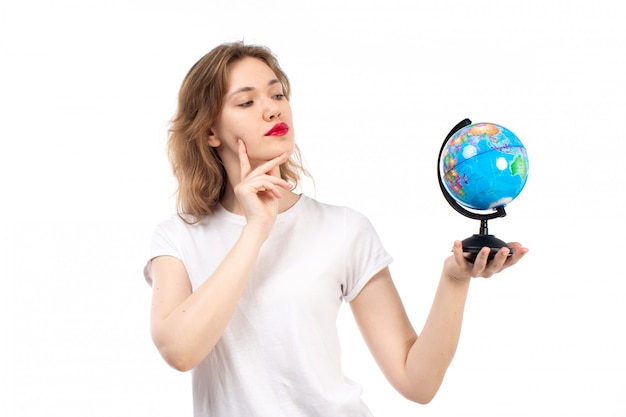 Вид спереди молодая дама в белой футболке держит маленький круглый глобус на белом
