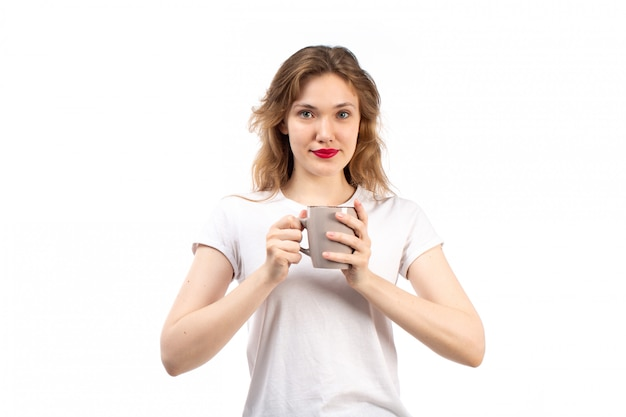 Вид спереди молодая леди в белой футболке, улыбаясь, держа чашку на белом