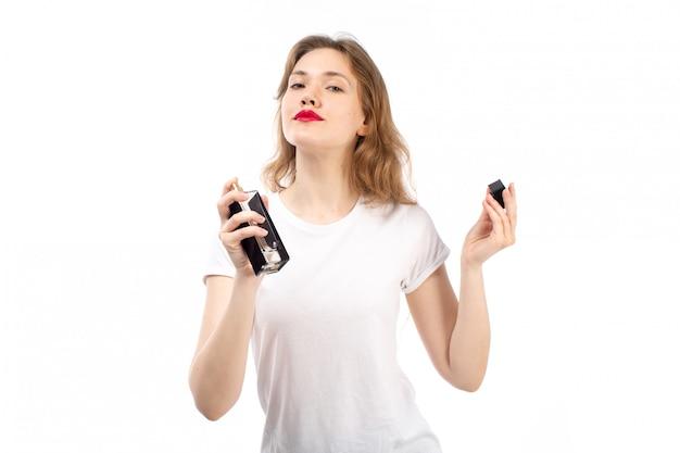 Вид спереди молодой леди в белой футболке с использованием черного парфюма на белом