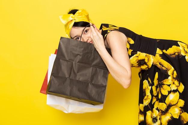 Вид спереди молодой леди в желто-черном цветочном платье с желтой повязкой на голове, держащей пакеты с покупками и проверяющей их на желтом