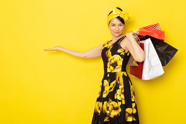 Вид спереди молодой леди в желто-черном цветочном платье с желтой повязкой на голове, держащей пакеты с покупками на желтом