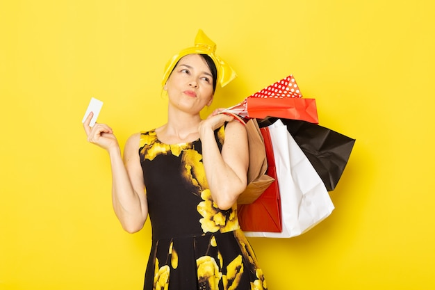 노란색-검은 꽃의 전면보기 젊은 아가씨는 노란색에 쇼핑 패키지를 들고 머리에 노란색 붕대로 드레스를 설계