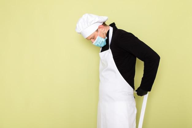 黒い手袋青い防護マスクで白い岬白いヘッドキャップを着ている黒いシャツを着た正面の若い男性料理人