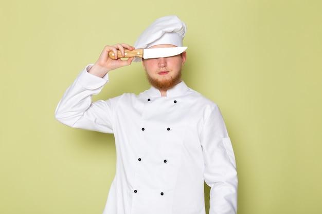 正面図の若い男性クックホワイトコックスーツホワイトヘッドキャップナイフで彼の目をカバー