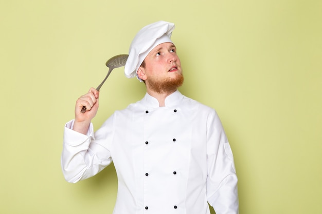 큰 은색 스푼 생각을 들고 흰색 요리사 양복 흰색 머리 모자에 전면보기 젊은 남성 요리사