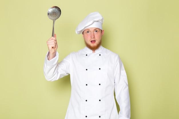 大きな銀のスプーンを保持している白いコックスーツホワイトヘッドキャップで正面の若い男性コック