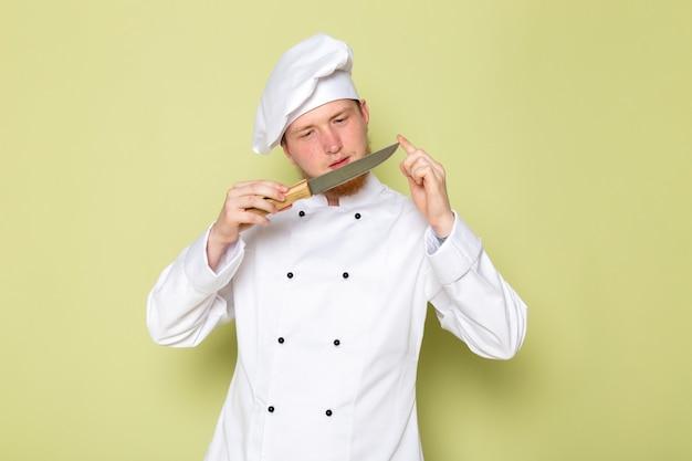 Вид спереди молодой мужской повар в белом костюме повара белая шапка держит проверочный нож