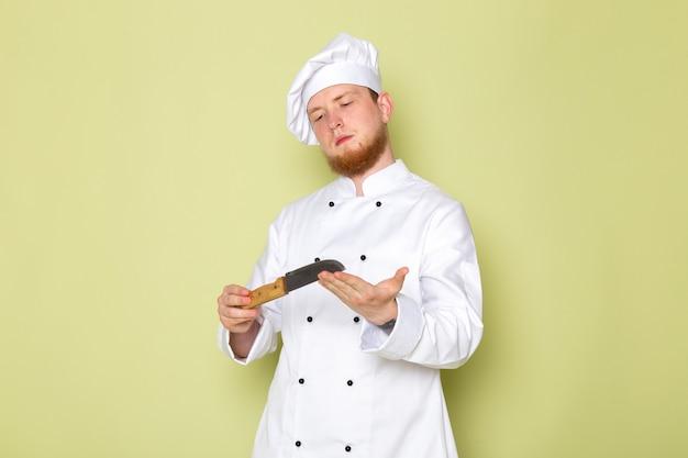 白いクックスーツホワイトヘッドキャップホールディングナイフで正面の若い男性クック