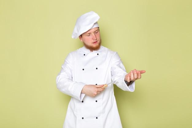 Вид спереди молодой мужчина повар в белом костюме повара белая шапка держит нож