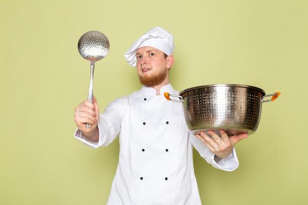 大きな銀のスプーンを笑顔で銀と金属の鍋を保持している白いクックスーツ白いヘッドキャップで正面の若い男性クック