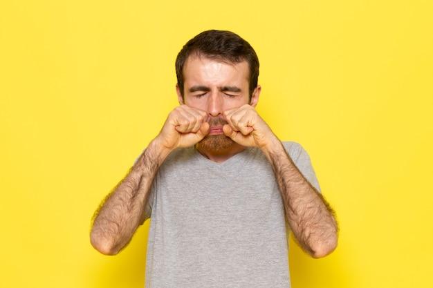 黄色の壁の男カラーモデル感情服で泣いている灰色のtシャツの偽の正面の若い男性