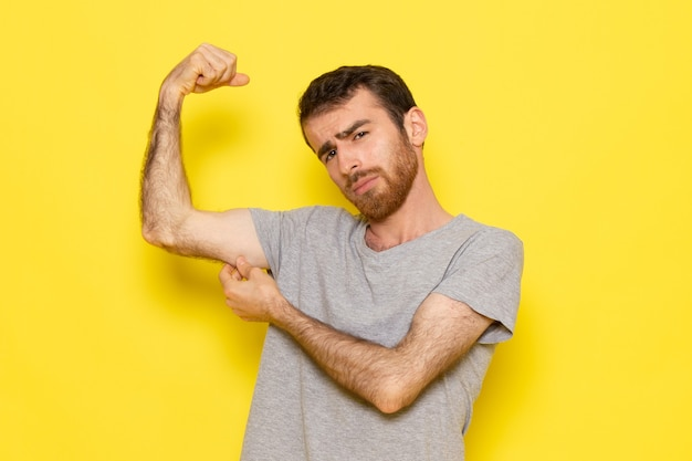灰色のtシャツの黄色の壁の男のカラーモデルの感情の服に屈曲の正面の若い男性