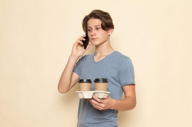 Молодой мужчина в серой футболке, держащий кофейные чашки и разговаривающий по телефону, вид спереди