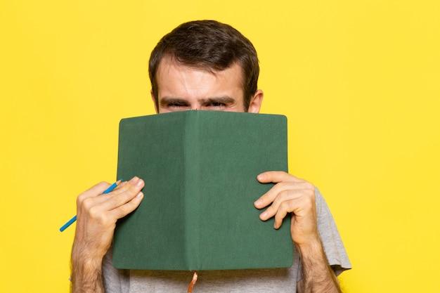 Вид спереди молодой мужчина в серой футболке, держащий зеленую тетрадь на желтой стене, цветная модель человека, одежда эмоций