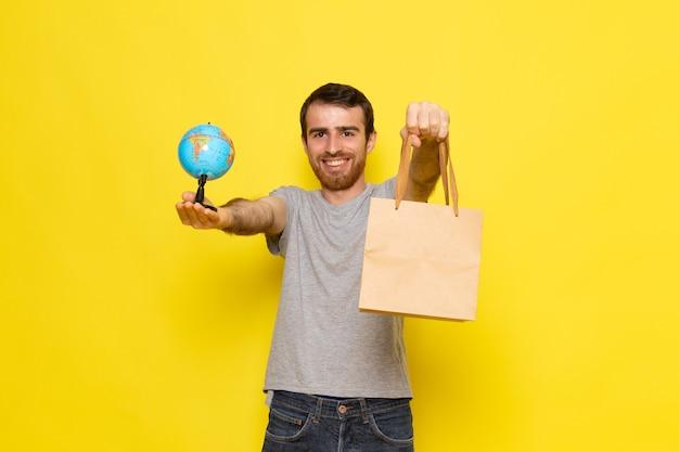 Вид спереди молодой мужчина в серой футболке, держащий маленький глобус и пакет с улыбкой на желтой стене, цветовая модель выражения эмоций человека