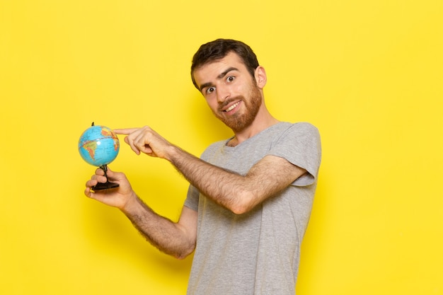 Вид спереди молодой мужчина в серой футболке, держащий маленький глобус с улыбкой на желтой стене, цветная модель, эмоция, одежда