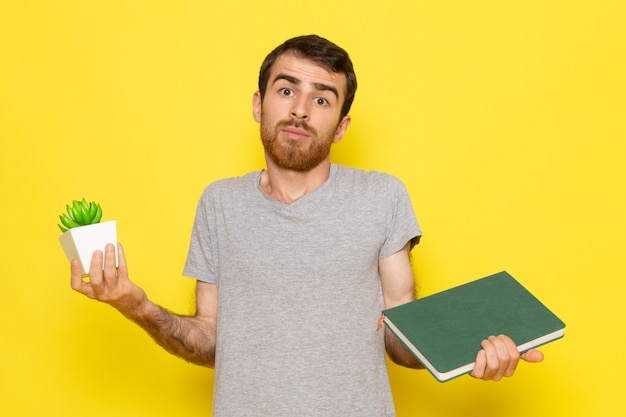 Вид спереди молодой мужчина в серой футболке, держащий растение и тетрадь на желтой стене, цветовая модель выражения эмоции человека