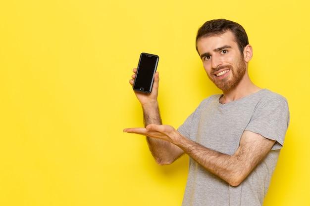 Молодой мужчина в серой футболке с улыбкой держит смартфон на желтой стене, цветная модель