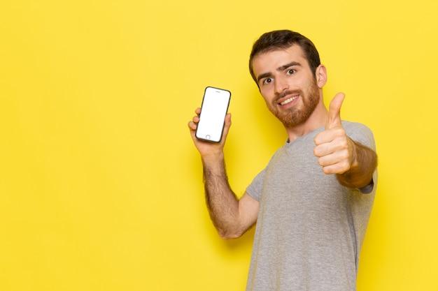 黄色の壁の男のカラーモデルで笑顔でスマートフォンを保持している灰色のtシャツの正面の若い男性