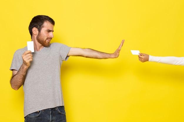 Молодой мужчина в серой футболке, держащий белую карточку, отказывается от другой белой карточки на желтой стене, цветная модель человека, эмоция, одежда