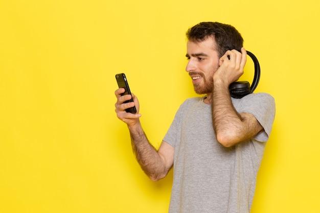 黄色の壁の男式感情カラーモデルで音楽を聴く灰色のtシャツの正面の若い男性