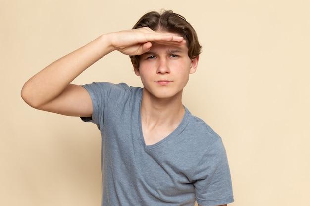 遠くを見ている灰色のtシャツの正面の若い男性