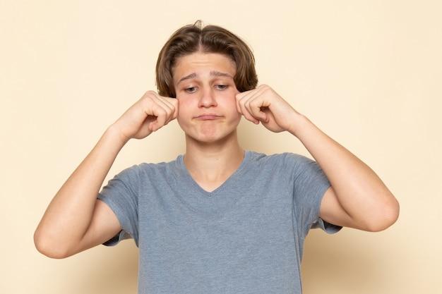 Молодой мужчина в серой футболке позирует и фальшиво плачет, вид спереди