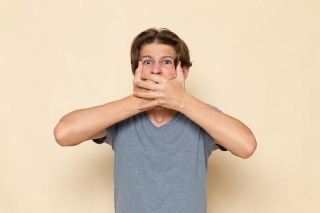 Молодой мужчина в серой футболке позирует, закрывая рот, вид спереди