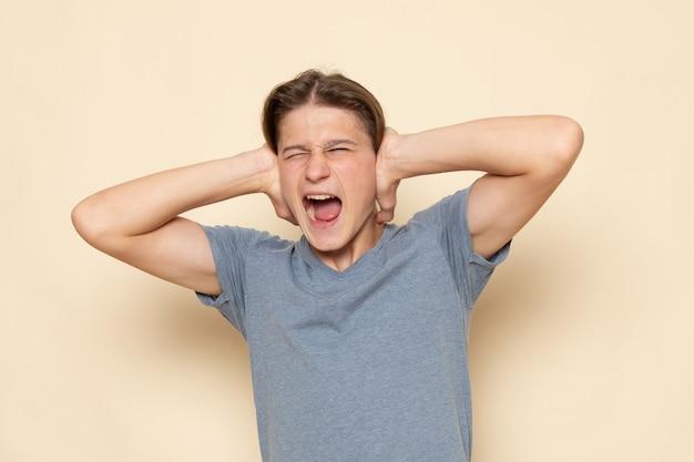 Молодой мужчина в серой футболке, вид спереди, кричит и закрывает уши