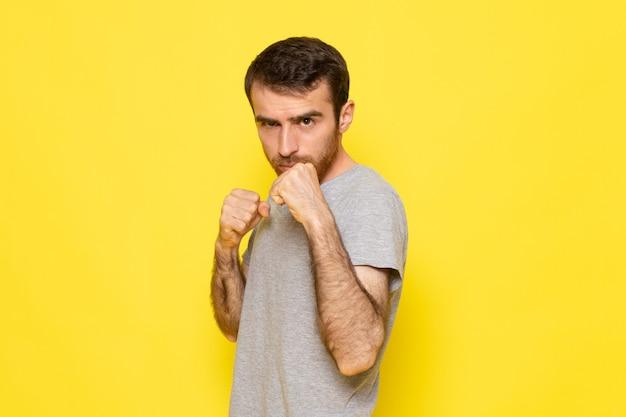 黄色の壁の男の表情感情カラーモデルのボクシングスタンドでポーズをとって灰色のtシャツの正面の若い男性
