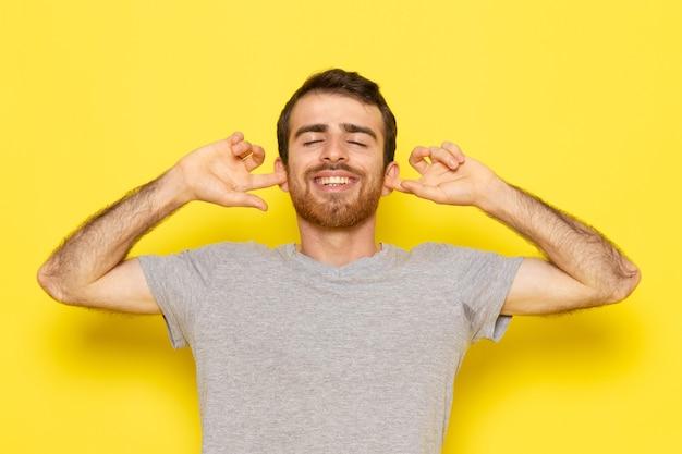 黄色の壁の男カラーモデル感情服に喜んで式でポーズグレーのtシャツで正面の若い男性