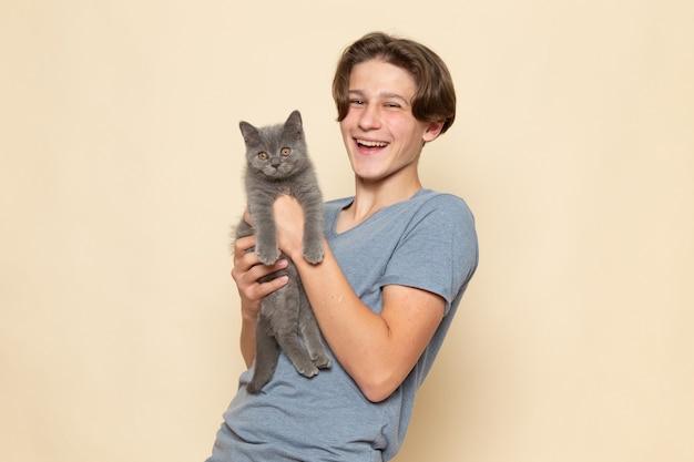 Молодой мужчина в серой футболке позирует со смехом, держа в руках симпатичного серого котенка