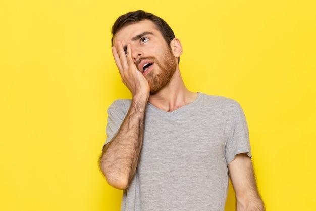 黄色の壁の男のカラーモデルで疲れた表情でポーズをとって灰色のtシャツの正面の若い男性