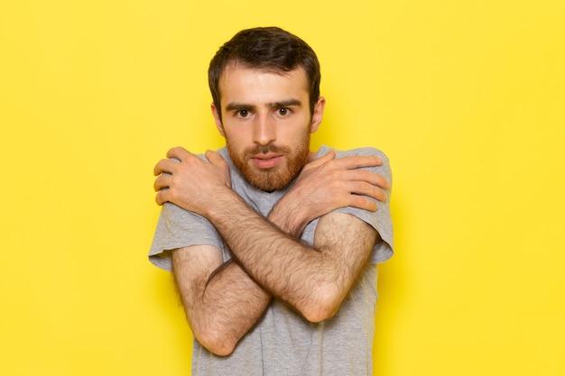Молодой мужчина в серой футболке, дрожащий на желтой стене, вид спереди, цветная модель, эмоция, одежда