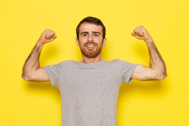 笑みを浮かべて、黄色の壁の男のカラーモデルの感情の服を曲げる灰色のtシャツで正面の若い男性