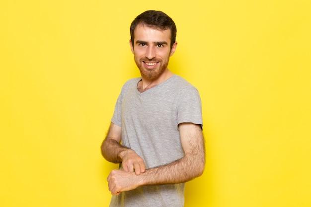 笑みを浮かべて、黄色の壁の男のカラーモデルの感情の服で彼の手首に指摘している灰色のtシャツの正面の若い男性