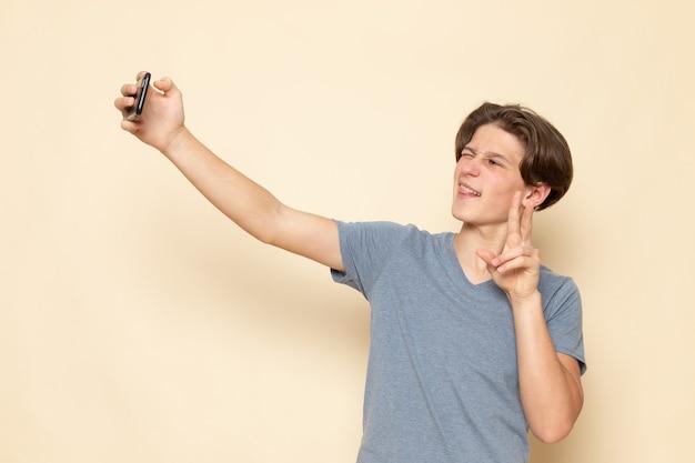 Молодой мужчина в серой футболке, делающий селфи, вид спереди