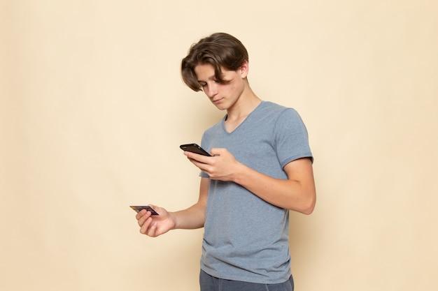 電話とホールディングカードを使用して灰色のtシャツの正面の若い男性