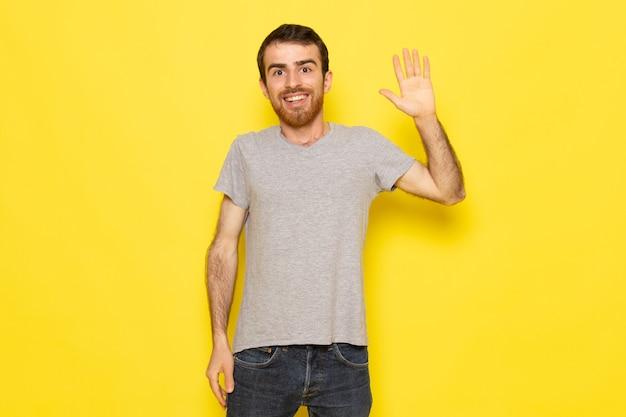 黄色の壁の男の表情感情カラーモデルに上げられた手で灰色のtシャツの正面の若い男性