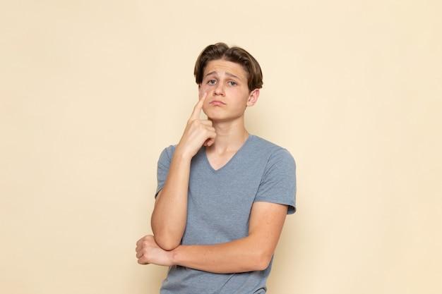 Молодой мужчина в серой футболке с грустным выражением лица, вид спереди