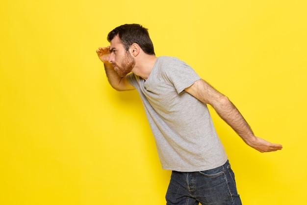 Вид спереди молодой мужчина в серой футболке с ищущим выражением лица на желтой стене. цветовая модель эмоции.