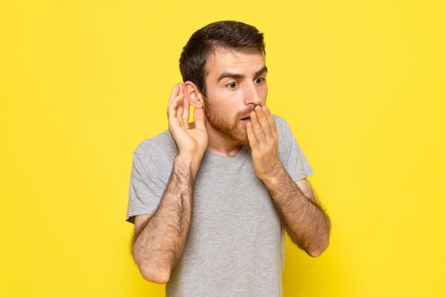 黄色の壁の男のカラーモデル感情服に驚いた表情で灰色のtシャツの正面の若い男性