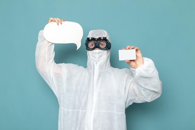 白の特別なスーツと白いカードを保持している正面図の若い男性と青い壁の男のスーツ危険特別装備色