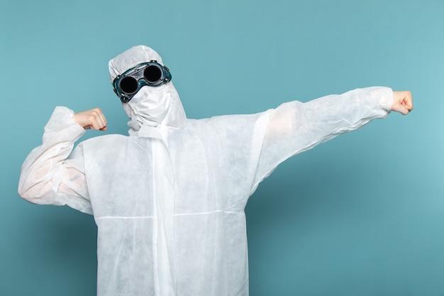 Вид спереди молодой мужчина в белом специальном костюме и уникальных защитных очках на синей стене в костюме опасного специального оборудования.