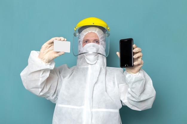 白い特別なスーツの正面図の若い男性と黄色の特別なヘルメット保持カードと青い壁の男の携帯電話の危険特別装備色