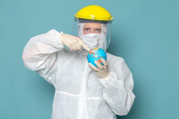 Вид спереди молодой мужчина в белом специальном костюме и желтом специальном шлеме, держащий земной шар на синей стене, мужчина костюм опасного специального оборудования цвета